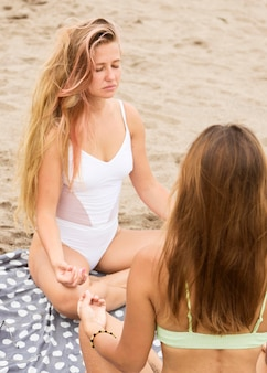 Two female friends meditating on the beach
