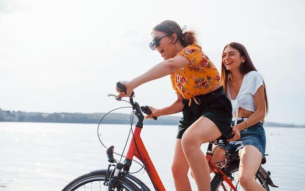 Две подруги на велосипеде развлекаются на пляже у озера.