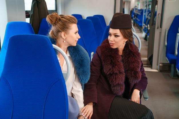 電車の中で2人の女性の友人