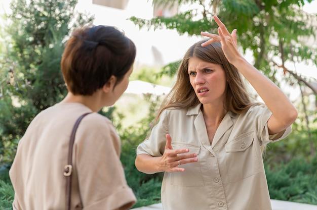 Две подруги на открытом воздухе общаются с помощью языка жестов