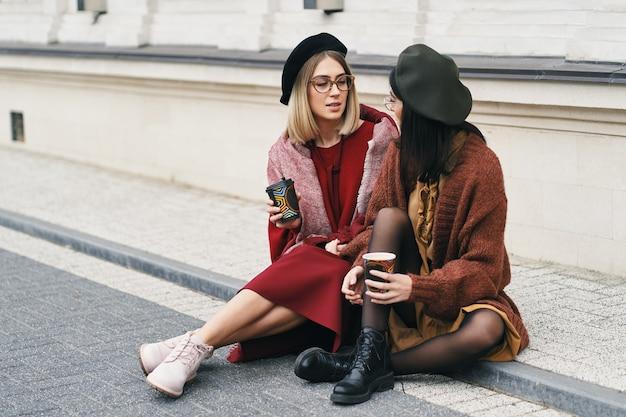 2人の女性の友人の屋外の肖像画。カジュアルな暖かい服装の女の子、都会のスティートに座って抱きしめているメガネとベレー帽、コピースペース。都市のライフスタイル、友情、姉妹関係のコンセプト。