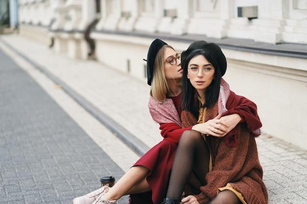 2人の女性の友人の屋外の肖像画。カジュアルで暖かい服装の女の子、都会のストリートに座って抱き締めるメガネとベレー帽、コピースペース。都市のライフスタイル、友情、姉妹関係のコンセプト。