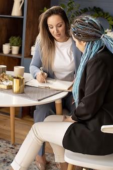 Две подруги-партнеры по сетевому бизнесу, продажа косметической продукции, серфинг в интернете, используют ноутбук