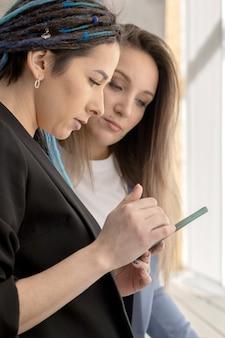 Две подруги-партнеры по сетевому бизнесу по продаже косметической продукции занимаются серфингом в интернете с помощью ноутбука