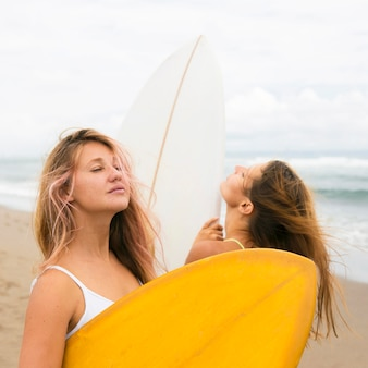 Две подруги позируют на пляже с досками для серфинга