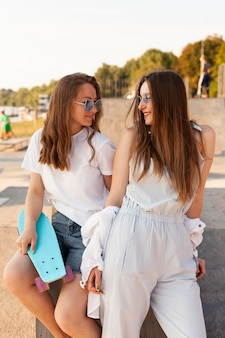 Two female friends posing together outdoors