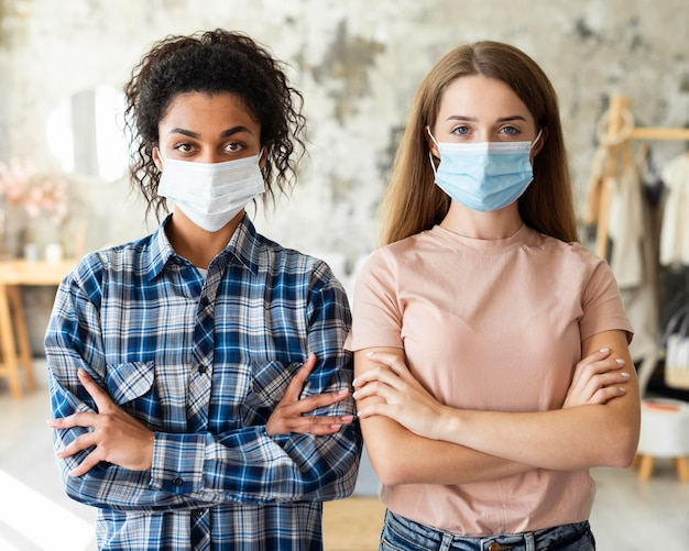 Two female friends posing together with medical masks on