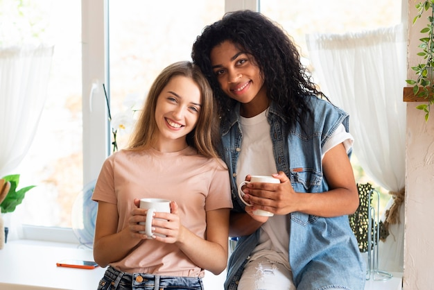 Two female friends posing together with mugs in the kitchen