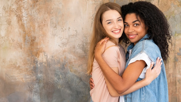 Two female friends posing while hugging with copy space