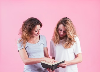 Two female friends reading book against pink background