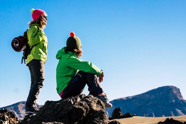 山でトレッキングしながらリラックスした2人の女性の友人。岩だらけの丘から山をリラックスして眺める2人の女性ハイカー。ハイキングツアーで休憩している友達