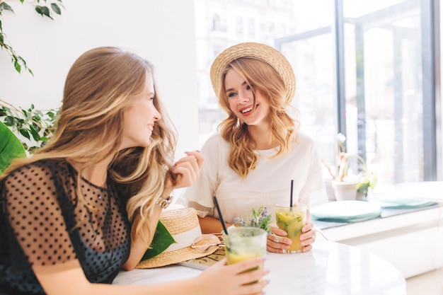 Two female friends resting together in favorite cafe and sharing news happy to see each other