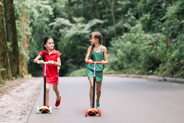 Two female friends riding push scooters on street