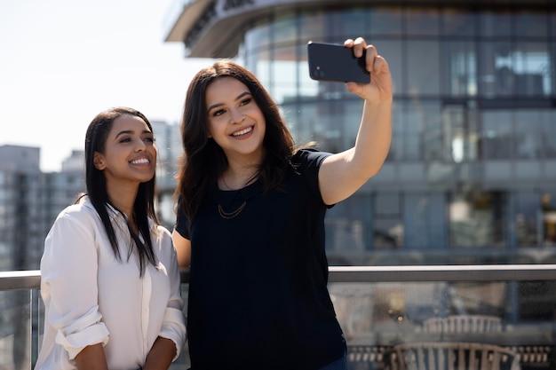 Due amiche su una terrazza sul tetto si fanno un selfie