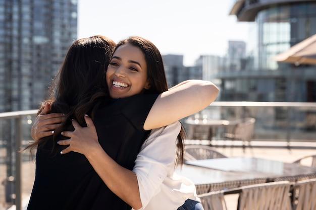 Due amiche che si vedono su una terrazza sul tetto e si abbracciano