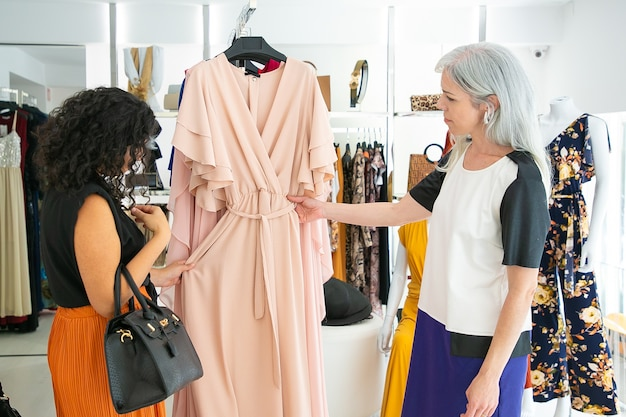 Due amiche che fanno shopping insieme, guardando sopra i vestiti appesi nel negozio di moda. acquirenti che toccano il nuovo vestito che appende sulla cremagliera. vista laterale. il consumismo o il concetto di acquisto
