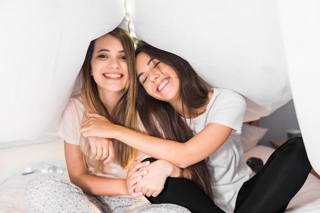 Due amici femminili seduti sul letto sotto la tenda bianca godendo
