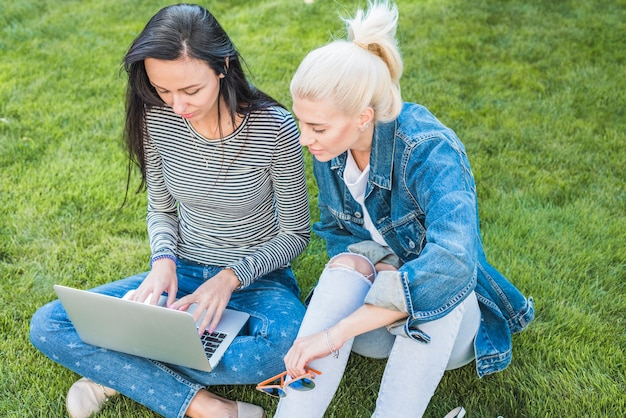 Two female friends sitting on green grass using laptop