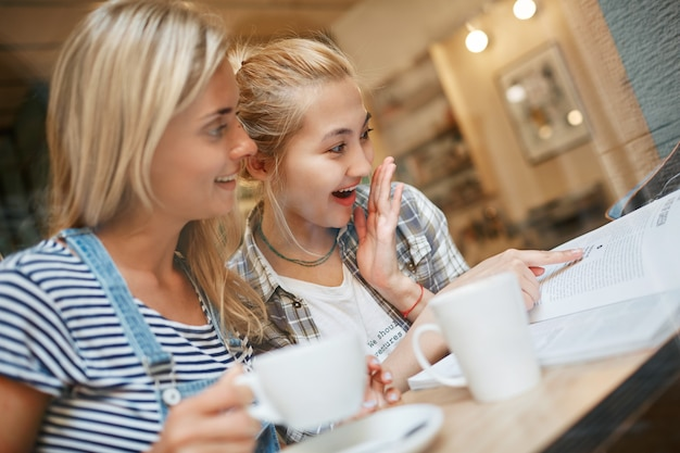 カフェの中に座ってコーヒーを飲んでいる2人の女性の友人