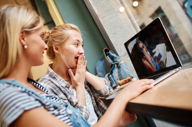 Due amici femminili che si siedono all'interno del caffè e che hanno caffè