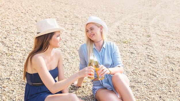 Две женщины-друзья, сидя на пляже, жарят бутылку с фруктовым пивом