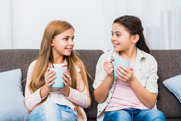 Two female friends sitting on sofa holding coffee mug in hand looking at each other