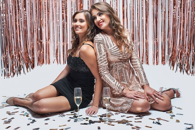 Two female friends sitting on white background and drinking champagne.