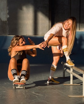 Two female friends skateboarding together