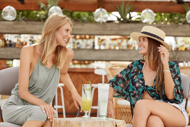 Two female friends spend spare time in cozy bar, dressed in summer clothing as going on beach, drink cold cocktails, looks happily at each other, share positive news.