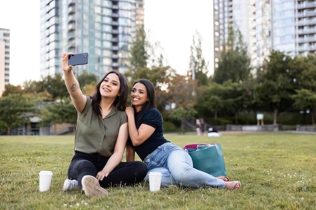 公園で一緒に時間を過ごして自分撮りをしている2人の女性の友人