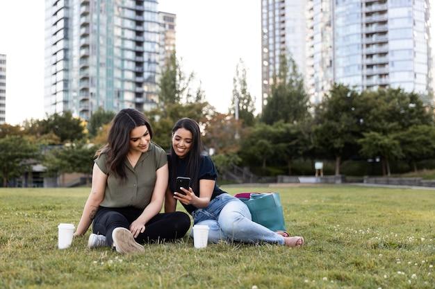 Две подруги проводят время вместе в парке и используют смартфон