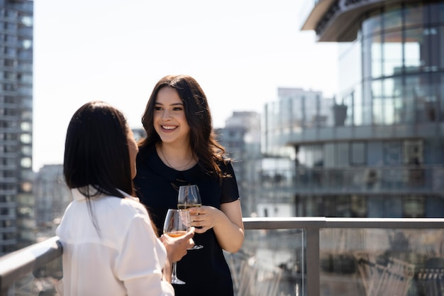 Two female friends spending time together and drinking wine on a rooftop terrace