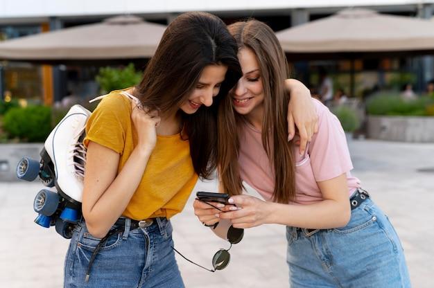 Две подруги проводят время вместе на открытом воздухе и несут роликовые коньки