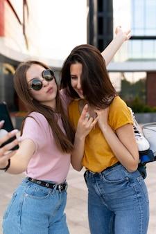 Две подруги проводят время вместе на открытом воздухе и делают селфи