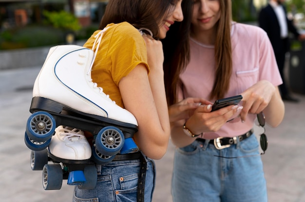 Two female friends spending time together outdoors and carrying roller skates