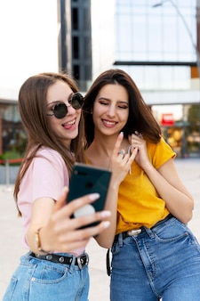 Two female friends spending time together outdoors and taking selfie