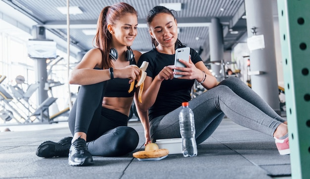 Two female friends in sportive clothes is in the gym earing fruits and using phone.