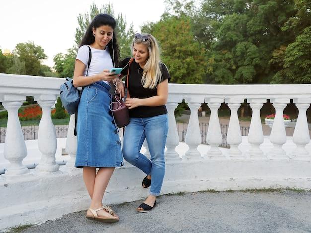 2人の女性の友人が公園に並んで立って、同じヘッドフォンで音楽を聴いています