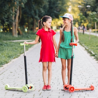 Two female friends standing on walkway with their push scooters