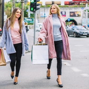Two female friends in stylish fur coat walking on street holding shopping bags