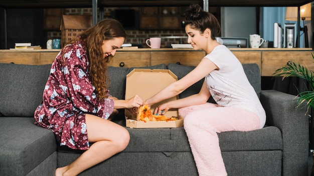 Two female friends taking pizza slices from box