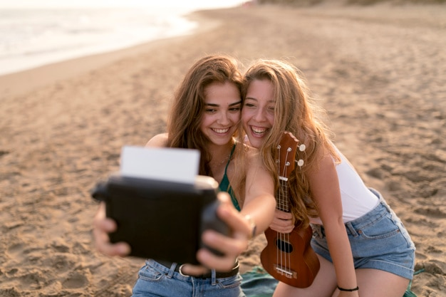 Two female friends taking self portrait from instant camera at beach