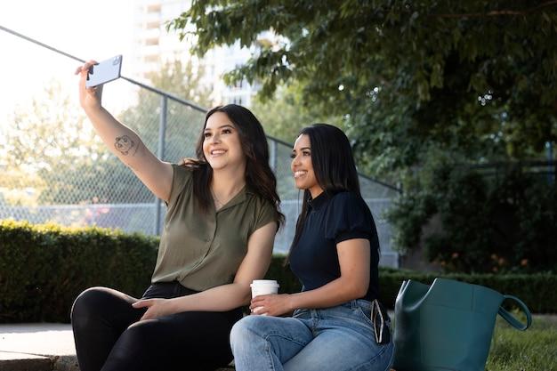 コーヒーを飲みながら公園で自分撮りをしている2人の女性の友人