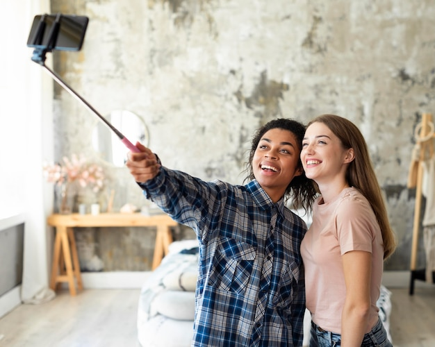 Two female friends taking a selfie together at home