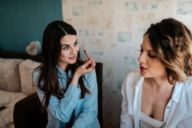 Two female friends talking and doing makeup at home.
