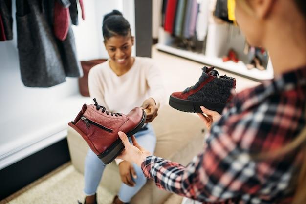 Две подруги примеряют обувь