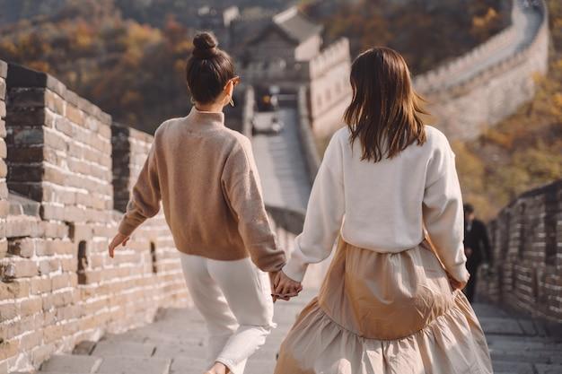 Две подруги прогуливаются вдоль великой китайской стены возле пешеходного перехода в пекине