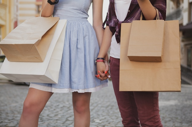 Two female friends walking in the city holding hands
