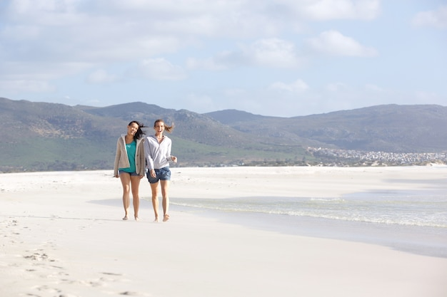 Two female friends walking on empty beach together