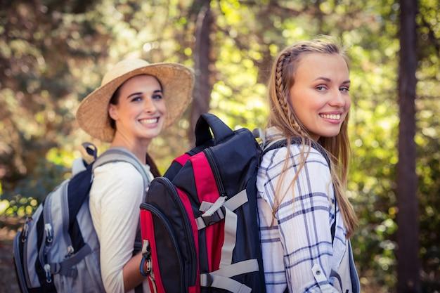 숲에서 함께 걷는 두 여자 친구